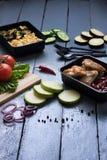 Zucchini fritto, melanzane, fagioli bolliti rossi con le ali di pollo arrostite, verdure crude intorno immagine stock