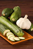 Zucchini and garlic. Closeup of a sliced zucchini and a garlic bulb head over a wooden table Royalty Free Stock Image