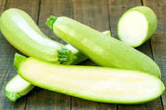 Zucchini. Green organic zucchinis on vintage wooden table Royalty Free Stock Photos