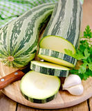 Zucchini green striped with a knife on board Stock Photo
