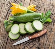 Zucchini mit Scheiben und Zucchiniblumen Lizenzfreie Stockfotografie