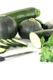 Zucchini mixed with parsley and knife. On a light background Stock Photography