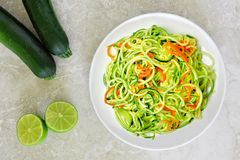 Zucchini noodles with carrots and lime on white marble Stock Image