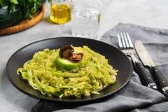 Zucchini Nudeln oder Zoodles mit sahniger Pilz-und Pesto-Soße stockfoto