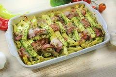 Zucchini och bacon bakad pasta med ost och parmesan i den vita krukan på den färgrika grönsaken för vit trätabell arkivbilder