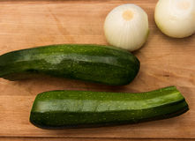 Zucchini & onions on a cutting board. Zucchini & onions on a wooden cutting board Stock Images
