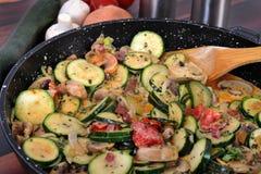 Zucchini, Onions and Mushrooms. Zucchini, tomatoes, onions and mushrooms cooking in a pan Stock Image
