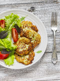 Zucchini pancake and fresh vegetable salad on white plate Stock Photos