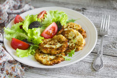 Zucchini pancakes and fresh vegetable salad in white plate Royalty Free Stock Image