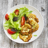 Zucchini pancakes and fresh vegetable salad on white plate Stock Image