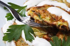 Zucchini pancakes with sour cream and parsley macro Stock Photography