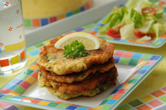Zucchini pancakes. Vegetable fritters served with fresh salad. Close up view. Royalty Free Stock Images