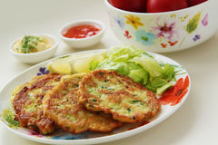 Zucchini pancakes. Vegetable fritters served with lemon and fresh salad. Yogurt and tomato sauces on background. Close up view. royalty free stock image