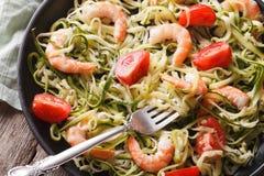 Zucchini pasta with shrimp and tomato macro. horizontal top view Royalty Free Stock Photos