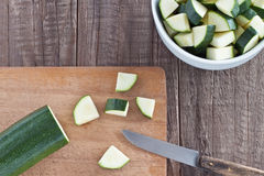 Zucchini pieces. Zucchini cut in pieces on a wooden board Stock Images