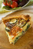 Zucchini Quiche. A slice of zucchini quiche on a wooden board stock photo