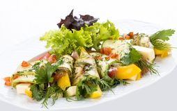 Zucchini rolls with cheese and vegetables on a white plate royalty free stock photos