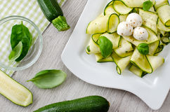 Zucchini salad with basil and mozzarella. Fresh zucchini and leaves of basil Stock Photos