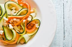 Zucchini salad with carrots, chickpeas and feta ch. Closeup with a zucchini salad with carrots, chickpeas and feta cheese, on a wooden table stock images