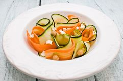 Zucchini salad with carrots, chickpeas and feta ch. Eese, on a wooden board royalty free stock photography