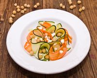 Zucchini salad with carrots, chickpeas and feta ch. Eese, on a wooden board royalty free stock images