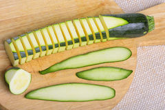 Zucchini. Sliced zucchini arranged on a wooden tray with stripes of its peel on one side Royalty Free Stock Image