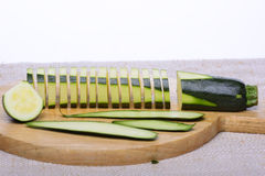 Zucchini. Sliced zucchini with stripes of peel arranged on a wooden tray Stock Image