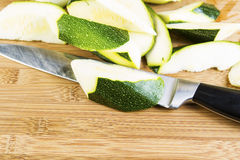 Zucchini Slices on Cutting board with Large Knife Stock Image