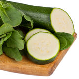 Zucchini and sorrel. Heap of fresh green sorrel with sliced raw zucchini on a wooden cutting board Stock Image