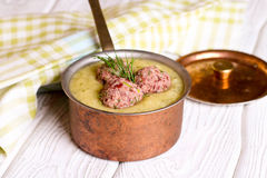 Zucchini soup close-up in saucepan and meatballs stock photo