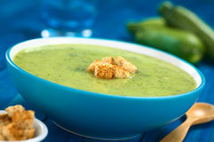 Zucchini Soup. Zucchini cream soup with wholewheat croutons served in blue bowl with wooden spoon on the side, zucchini and glass in the back (Selective Focus royalty free stock image