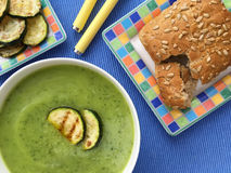 Zucchini soup. Vegetable courgette soup served with grilled slices of zucchini and wholegrain baguette. Top view. Vegetable zucchini soup puree ang grilled Stock Photography