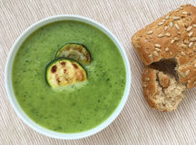 Zucchini soup. Vegetable courgette soup served with grilled slices of zucchini and wholegrain baguette. Top view. Vegetable zucchini soup puree with grilled Stock Images
