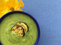 Zucchini soup. Vegetable soup puree with grilled slices of zucchini and zucchini flowers on background. Top view. Vegetable zucchini soup puree ang grilled Royalty Free Stock Photos