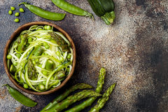 Zucchini spaghetti or noodles zoodles bowl with green veggies. Top view, overhead, copy space. stock image