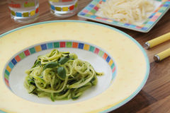 Zucchini spaghetti with pesto and parmesan cheese. Wooden background. Close up view. stock images