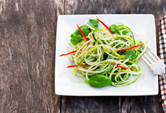 Zucchini  spaghetti salad with basil and paprica on squared plat Stock Photography