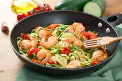 Zucchini noodles sauteed with cherry tomato and prawns in a pan. Zucchini spaghetti sauteed with tomato cherry and prawns in a pan on a rustic wooden table Royalty Free Stock Photos