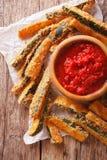 Zucchini sticks in breadcrumbs and tomato sauce closeup. vertica Stock Photos