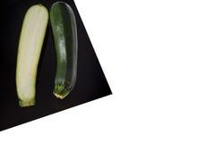 Zucchini sullo strato nero isolato su bianco immagine stock libera da diritti
