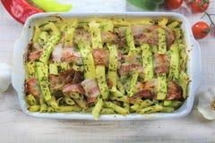 Zucchini und Speck backten Teigwaren mit Käse und Parmesankäse im weißen Topf auf dem bunten Gemüse des weißen Holztischs stockfotografie