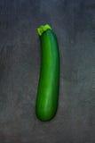 Zucchini verde fresco isolato sul backgroun scuro della pietra dell'ardesia Immagine Stock