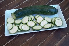 Zucchini in a white tray on wood royalty free stock images