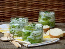 Zucchini with yogurt sauce and fresh dill. In jars with slices of bread on a wooden background stock photos