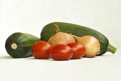 Zucchinier, lökar och tomater på en vit bakgrund Arkivfoton