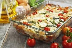 Zucchinin bakade I med höna, körsbärsröda tomater och örter Arkivfoto