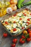 Zucchinin bakade I med höna, körsbärsröda tomater och örter Arkivfoton
