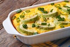 Zucchinin bakade med ost, ägg och lökcloseupen Royaltyfri Foto