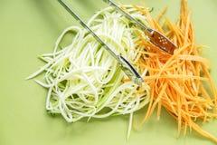 Zucchinin och moroten röra sig i spiral på grön skärbräda Royaltyfria Bilder