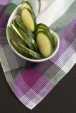 Zucchinin skivade ‹för †på rosa skotsk plädbordduk Arkivfoton
